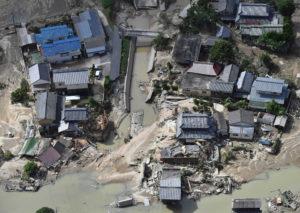 川からあふれた水で壊れた家の写真