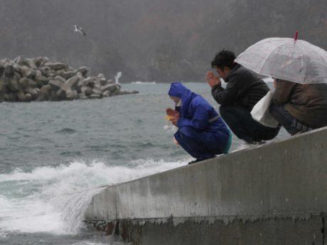 津波で亡くなった人たちに向けてお祈りをする人たちの写真