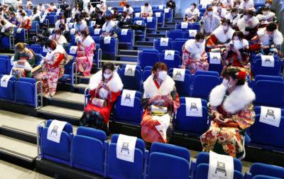 成人式の会場で お互いに離れて座る 参加者たち